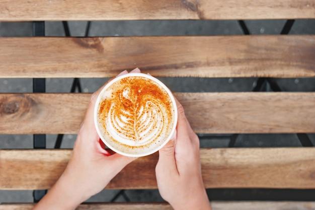 Frau, die eine papierschale mit kaffee hält.