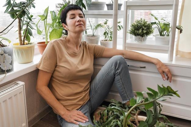Frau, die eine pause von der pflege der zimmerpflanzen macht