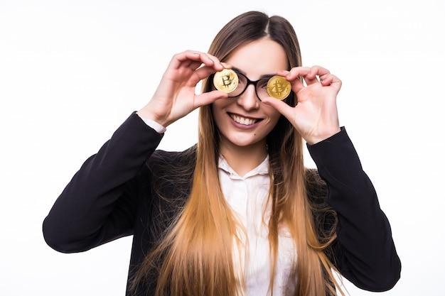 Frau, die eine physische kryptowährung der bitcoin-münze in ihrer hand vor ihren augen hält