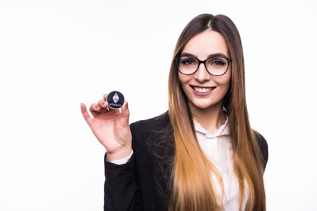 Frau, die eine physische kryptowährung der ethereum-münze in ihrer hand hält
