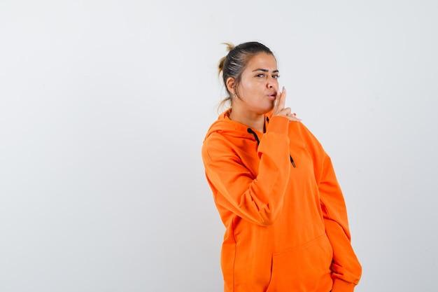 Frau, die eine pistolengeste im orangefarbenen hoodie zeigt und selbstbewusst aussieht