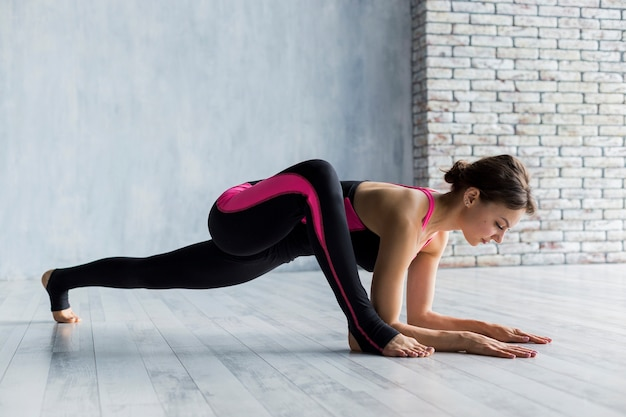 Frau, die eine planke mit dem bein verlängert in der frontseite durchführt
