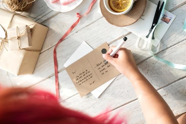 Frau, die eine postkarte schreibt