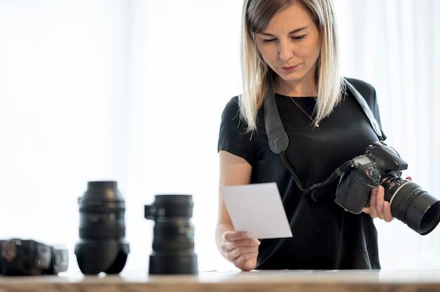 Frau, die eine professionelle kamera und ein foto hält