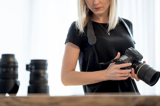 Frau, die eine professionelle kamera und ein objektiv hält