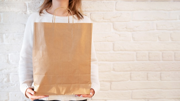 Frau, die eine recycelbare papiertüte hält. recycling-idee