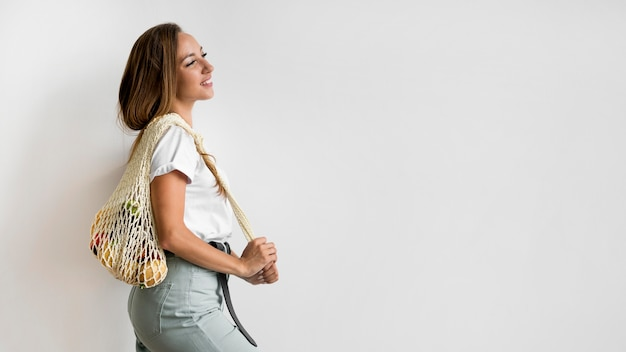 Frau, die eine recycelbare tasche mit kopienraum hält