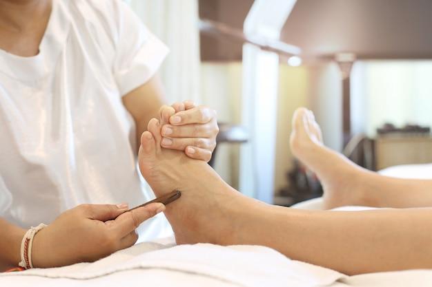 Frau, die eine reflexology-fußmassage empfängt