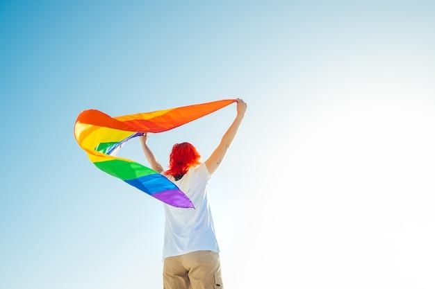Frau, die eine regenbogenfahne des schwulen stolzes hält, die gegen die aufgehende sonne auf blauem himmelhintergrund flattert