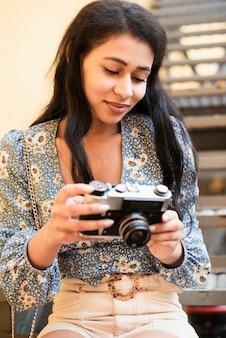 Frau, die eine retro- kamera hält und fotos betrachtet