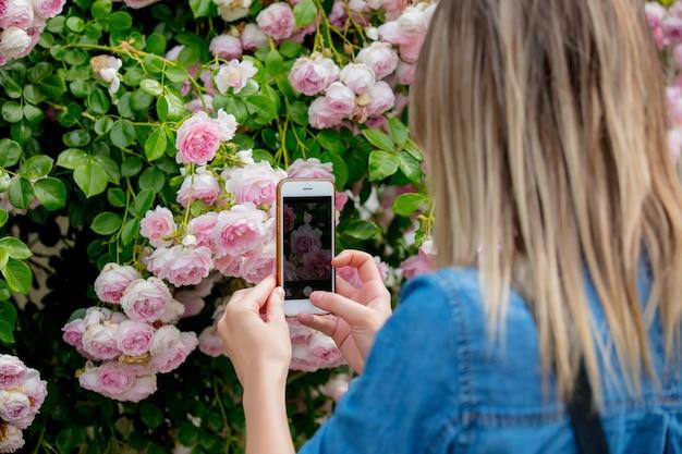 Frau, die eine rose mit dem telefon fotografiert. seitenansicht