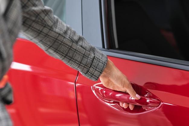 Frau, die eine rote autotür öffnet
