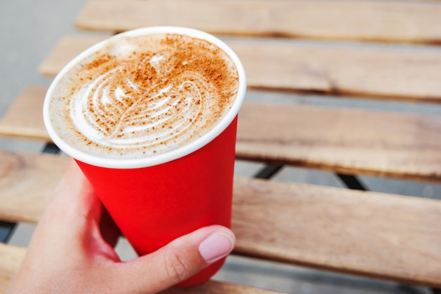 Frau, die eine rote papierschale mit kaffee hält.