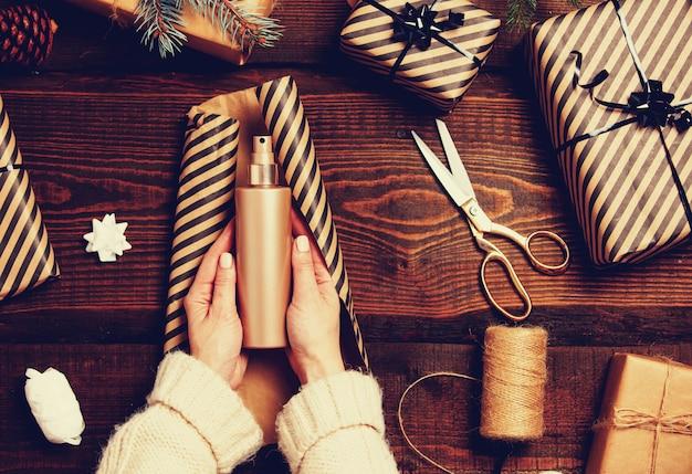 Frau, die eine sahneflasche als weihnachtsgeschenk einwickelt