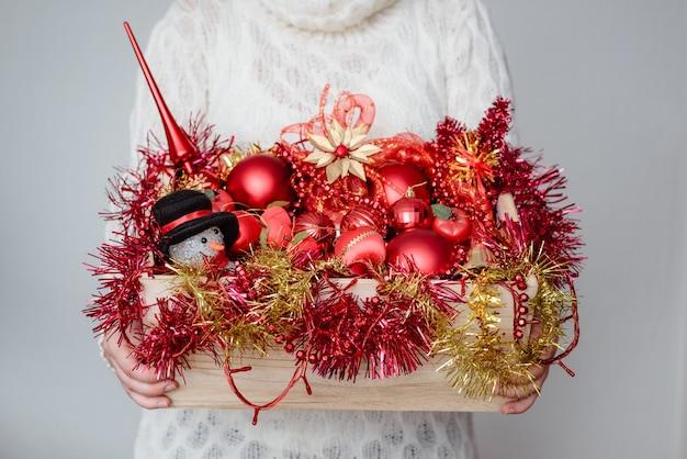 Frau, die eine schachtel der roten weihnachtsverzierungen hält