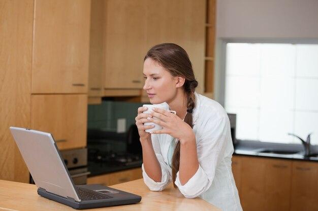 Frau, die eine schale beim betrachten eines computers hält