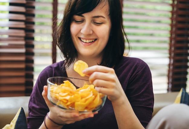 Frau, die eine schüssel chips genießt