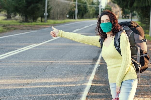 Frau, die eine schützende gesichtsmaske per anhalter auf einer landstraße trägt.