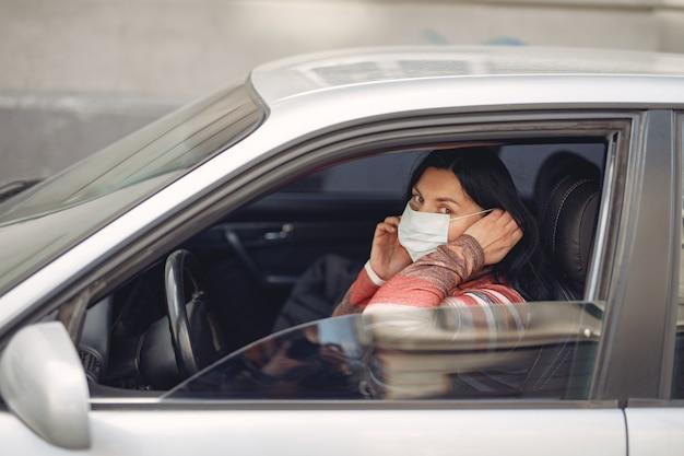 Frau, die eine schutzmaske sitzt, die in einem auto sitzt