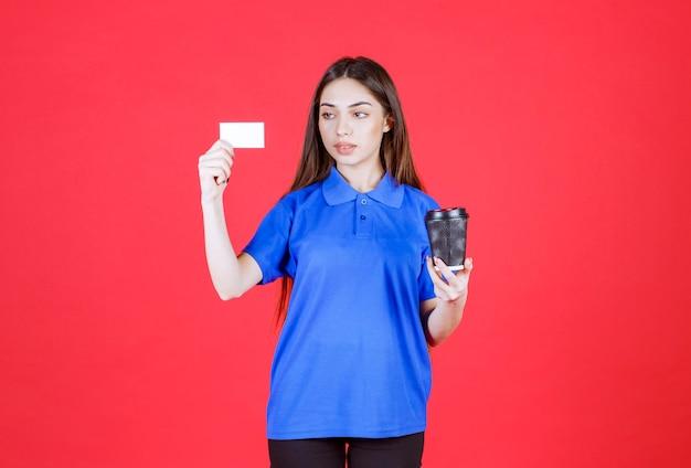 Frau, die eine schwarze wegwerfkaffeetasse hält und ihre visitenkarte vorlegt.