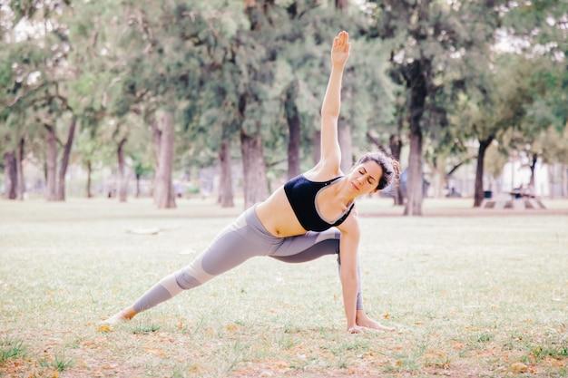 Frau, die eine seitenplanke yoga-pose im freien tut. pilates gesunder lebensstil für menschen in yoga-übungen. training im freien und fit bleiben konzept. menschen, die wohlfühlmeditation im park machen.