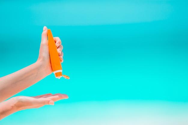 Frau, die eine sonnencreme hält und und ihre hand mit sonnencreme auf einem tropischen strand reibt