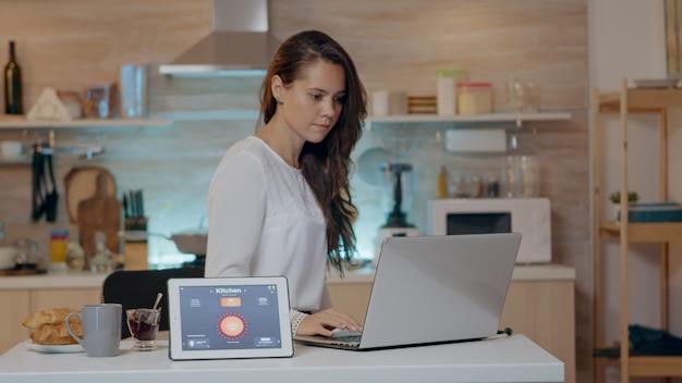 Frau, die eine sprachaktivierte intelligente drahtlose beleuchtungs-app auf einem tablet verwendet