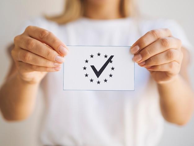 Frau, die eine stimmzettelnahaufnahme hält