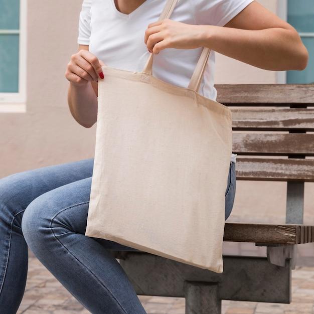 Frau, die eine stofftasche im freien trägt