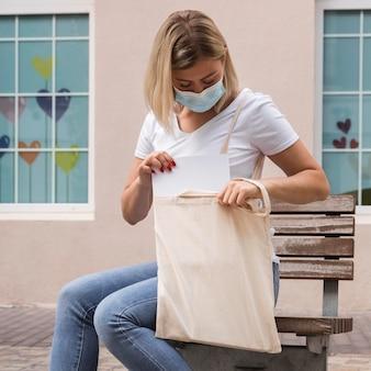 Frau, die eine stofftasche trägt und auf bank sitzt