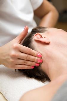 Frau, die eine stressabbau-druckpunktmassage auf ihrem nacken durch einen gesundheitstherapeuten erhält