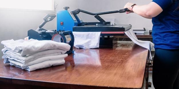 Frau, die eine sublimationsmaschine manipuliert, die ein hemd bügelt. werbe- und siebdruckkonzept.