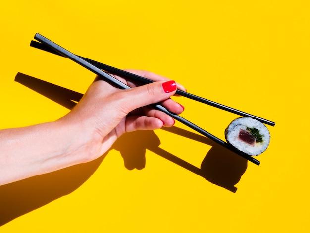 Frau, die eine sushirolle auf einem gelben hintergrund hält