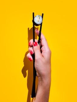 Frau, die eine sushirolle in einem paar essstäbchen hält