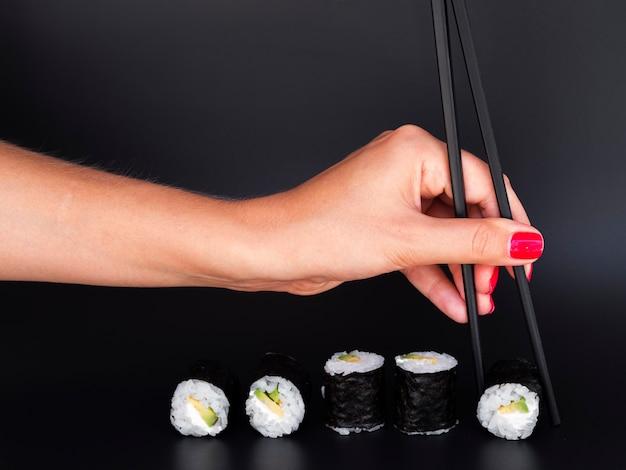 Frau, die eine sushirolle mit essstäbchen auswählt