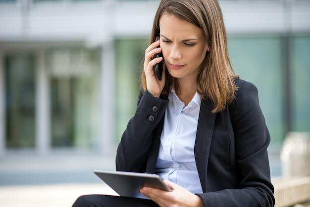 Frau, die eine tablette bei der unterhaltung an ihrem mobilhandy vor ihrem büro verwendet