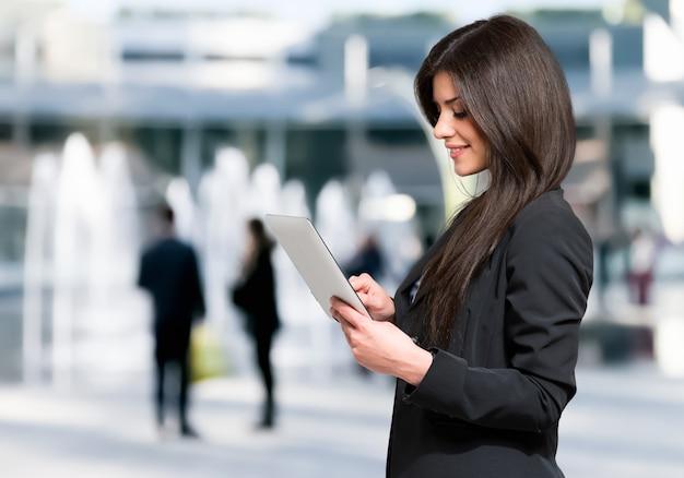 Frau, die eine tablette im freien in einer modernen städtischen landschaft verwendet