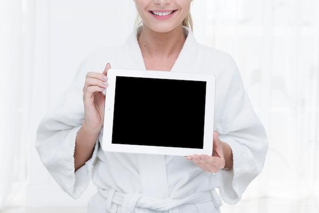 Frau, die eine tablette in einem badekurort verwendet