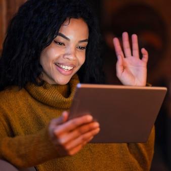 Frau, die eine tablette in einem café für einen videoanruf verwendet