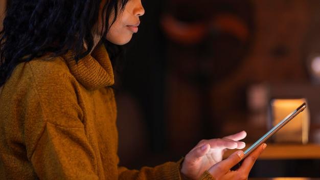 Frau, die eine tablette in einem kaffeegeschäft verwendet