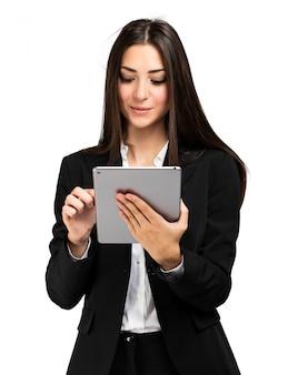 Frau, die eine tablette lokalisiert auf weißer wand verwendet