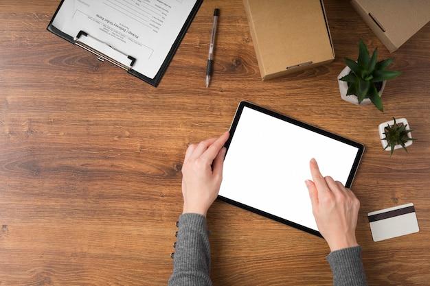 Frau, die eine tablette mit einem leeren bildschirm mit kopienraum verwendet