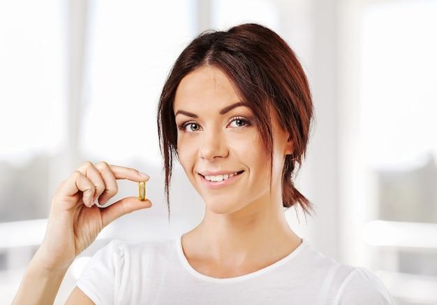 Frau, die eine tablette nimmt. nahaufnahme hand mit einer pille und dem mund, auf hintergrund isoliert