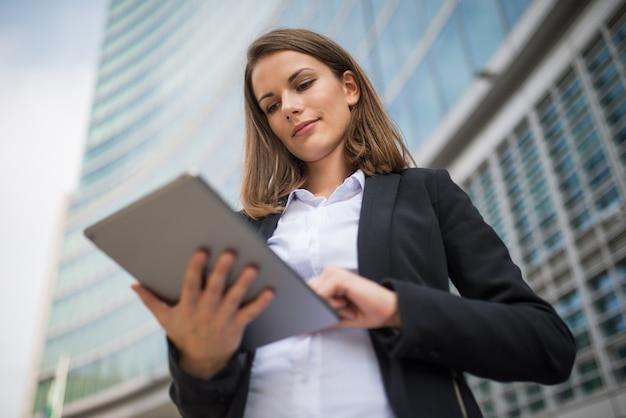 Frau, die eine tablette vor ihrem büro verwendet