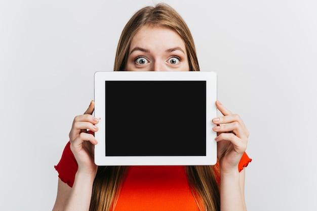 Frau, die eine tablette vor ihrem gesichtsmodell hält