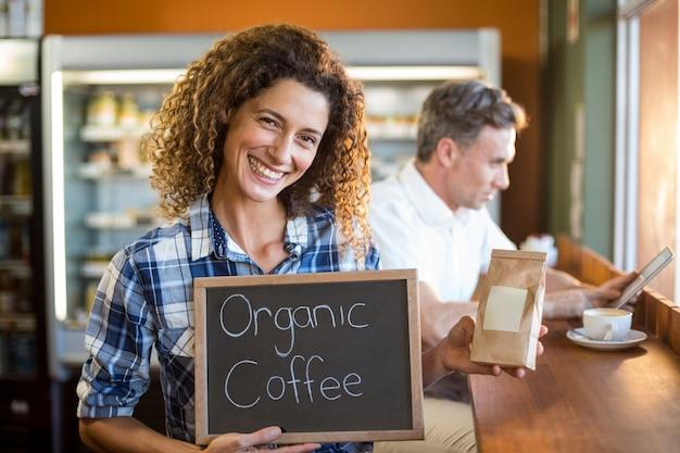 Frau, die eine tafel hält, die bio-kaffee liest