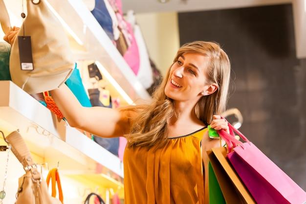 Frau, die eine tasche im mall kauft