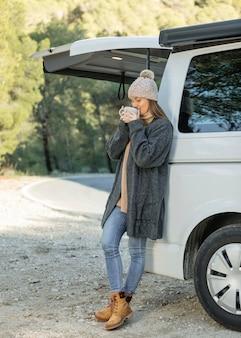 Frau, die eine tasse des getränks während auf einer straßenreise genießt