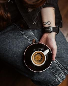 Frau, die eine tasse espresso auf ihren beinen hält