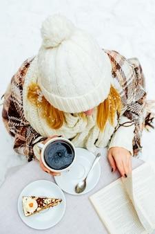 Frau, die eine tasse heißen kaffee auf rustikalem holztisch hält, nahaufnahme von händen in warmem pullover mit tasse, wintermorgenkonzept, draufsicht